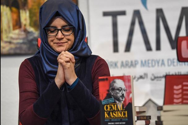 Hatice Cengiz, la fiancée de Jamal Khashoggi, est assise à côté du livre qu'elle lui a consacré après son assassinat, en 2019(AFP)